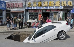 Bystanders look at a car that has partially fallen into a small sinkhole along a street in Beijing